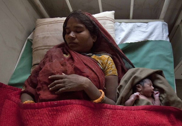 Anguri rests on a bed along with her newborn baby in the post delivery ward at a community health centre in Madhya Pradesh