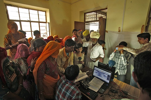 Villagers crowd inside an enrolment centre for the Unique Identification (UID) database system at Merta district in the desert Indian state of Rajasthan February 21, 2013. In a more ambitious version of programmes that have slashed poverty in Brazil and Mexico, the Indian government has begun to use the UID database, known as Aadhaar, to make direct cash transfers to the poor, in an attempt to cut out frauds who siphon billions of dollars from welfare schemes. Picture taken February 21, 2013. REUTERS/Mansi Thapliyal (INDIA - Tags: BUSINESS SOCIETY POVERTY SCIENCE TECHNOLOGY) - RTR3EDSK
