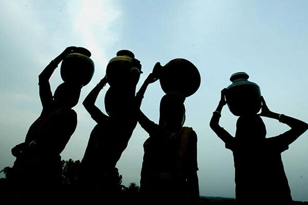 Indian women carry water pots to collect drinking water in Purulia,300km (186 miles) west from the eastern Indian city of Calcutta, June 5, 2003. Indians prayed for rain at temples and mosques as the death toll from a heat wave sweeping the country neared 1,150 on Wednesday. The United Nations marked world environment day on Thursday with a focus on water, saying two billion people were dying for it. REUTERS/Jayanta Shaw    PP03060014 JS/DL - RTROWEA